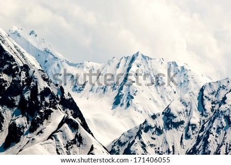 Mountainous landscape in Switzerland with snowy peaks in summer.