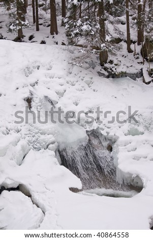 mountainous stream covered with snow