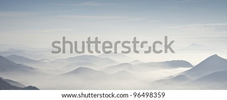 Mountains A view of a group of mountains, surrounded by a dense fog. - stock photo