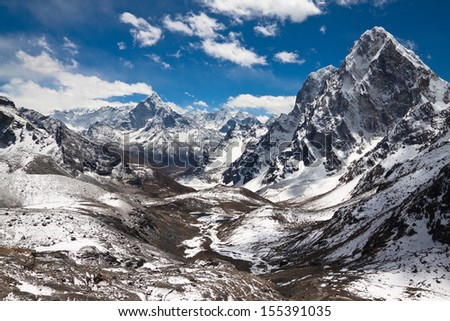 Mountains Ama Dablam, Cholatse, Tabuche Peak at the blue sky with clouds on a sunny day - stock photo