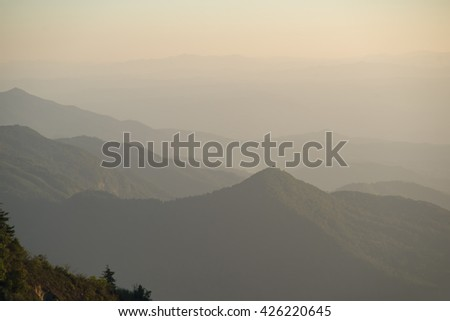 mountains and a valley in a foggy morning - stock photo