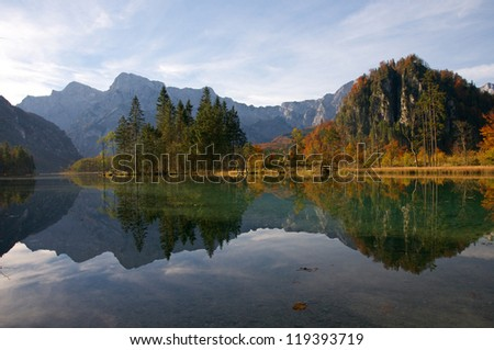 mountains and autumn forest mirroring in the lake