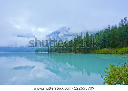 mountains and pines reflection in a glacial lake Kucherlinskoe, Altai, Siberia, Russia - stock photo