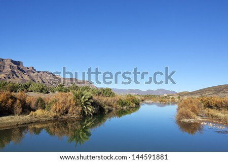 Mountains and river with reflections against clear blue sky. - stock photo