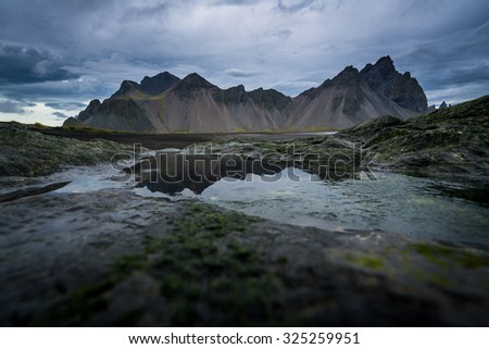 Mountains and volcanic lava sand dunes by the sea in Stokksness, Iceland. - stock photo