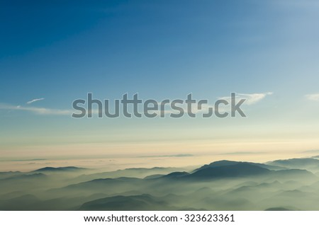 mountains clouds blue sky and fog photographed from on mountaintop - stock photo