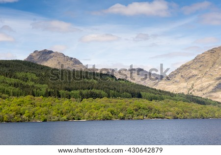 Mountains covered in woodland rise from the banks of Loch Lomond in the West Highlands of Scotland. - stock photo
