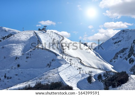Mountains covered with snow and ski track on the slope in popular tourist resort of Limone Piemonte in Italy. - stock photo