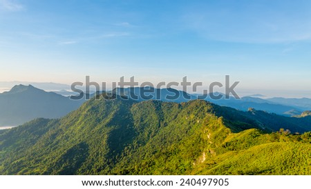 Mountains green grass and blue sky landscape - stock photo