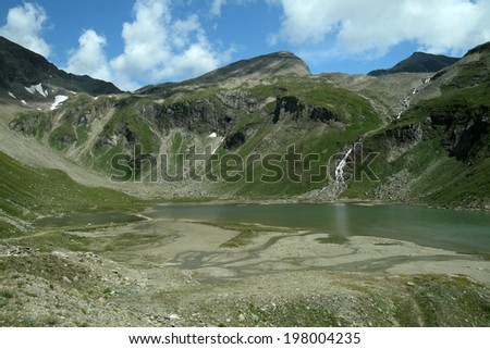 Mountains in Austria. Green grass, rocks and water