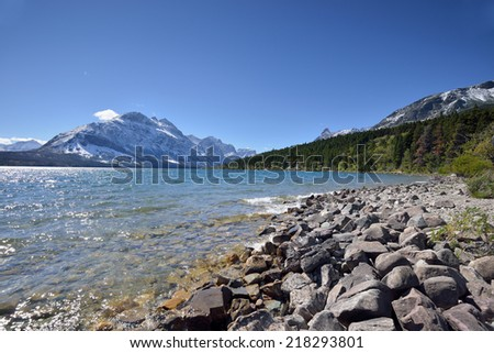Mountains in  Glacier National Park, Montana, USA rise above St. Mary Lake as water laps against the rocks in the foreground - stock photo