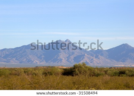 Mountains in the background, with a desert foreground - stock photo