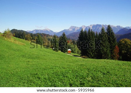 Mountains int he distance with green field in the foreground - stock photo
