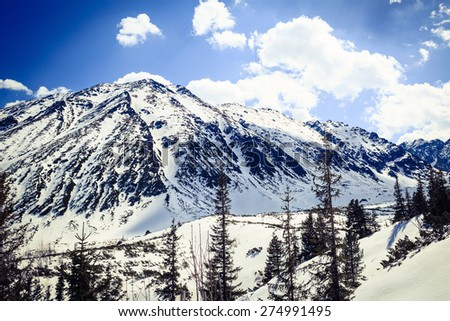 Mountains landscape in winter in Tatras. Mountain ridge over blue sunny sky, Poland - stock photo