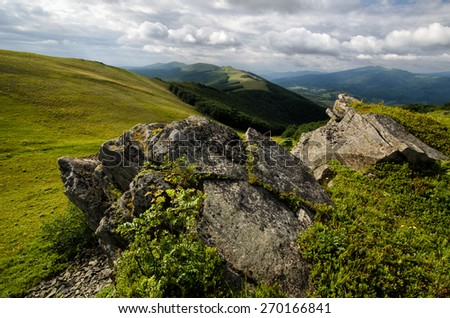 Mountains landscape with grassy hills and slopes and cloudy sky - stock photo