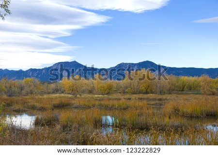Mountains near Boulder, Colorado rise up above the nearby Walden Ponds wildlife refuge park - stock photo