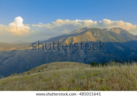 Mountains near Xylokastro, Corinthia, covered in green trees against a partly cloudy sky.