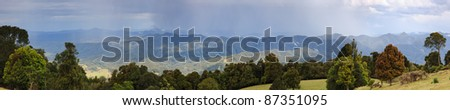 mountains rain-forest wide panorama over hills and trees and clouds with running rain - stock photo