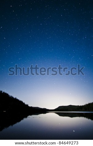 Mountains Reflected in a Still Lake with the Stars Above - stock photo
