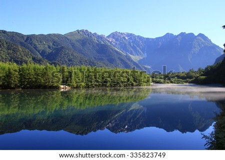 Mountains reflected in the lake - stock photo