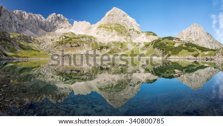 Mountains reflecting in Lake Drachensee near Coburger Hut, Ehrwald, Tirol, Austria - stock photo