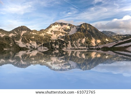 Mountains reflecting in water - stock photo