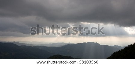 Mountains silhouette and sun rays - stock photo
