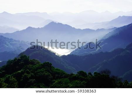 mountains surround lake with light fog. The lake surface reflect sunshine. - stock photo