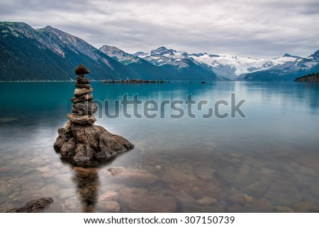 Mountains surrounding Turquoise lake with rock pile