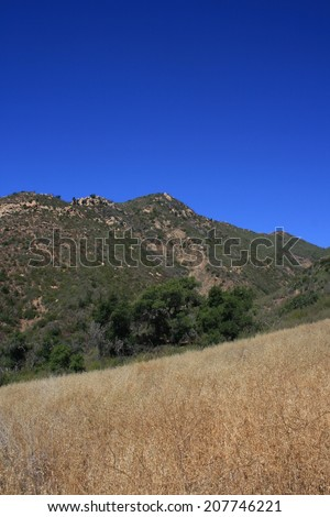 Mountains towering above a sloping field on a hill, California - stock photo
