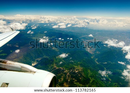 Mountains under the wing of the aircraft. mountain peaks covered with green meadows in the clouds - stock photo