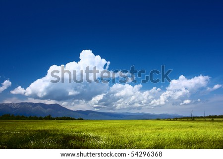 Mountains valley and blue sky with fluffy clouds - stock photo
