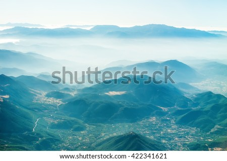 mountains view through airplane window at high altitude. Cloudy sky. Mountains in the clouds - stock photo