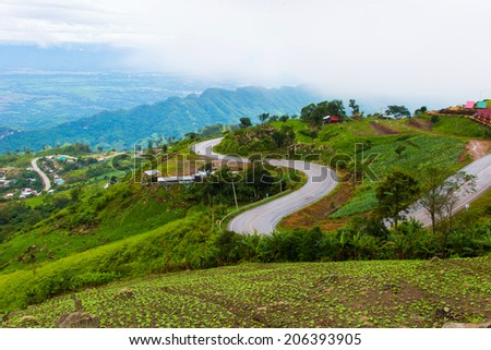 mountains view under mist and curve road in the morning ,Phetchabun, Thailand - stock photo