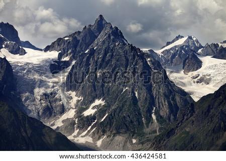 Mountains with glacier in clouds before rain. Caucasus Mountains. Georgia, region Svanetia. - stock photo