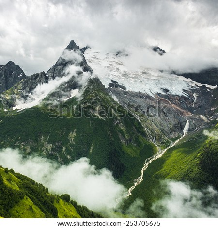 mountains with green grass snow and stormy sky landscape - stock photo