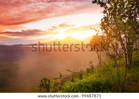 Mountains with lake and green lush meadow with tree on a hill side - stock photo