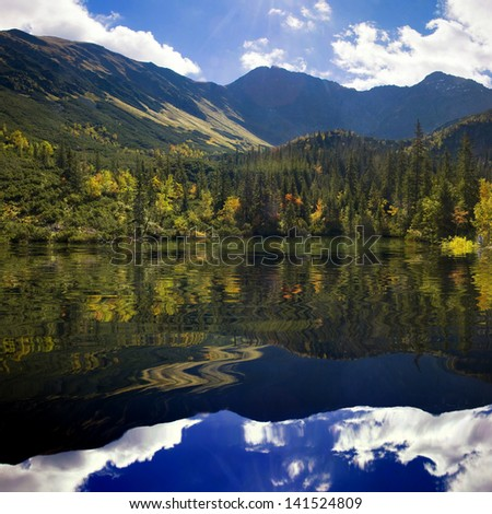 Mountains with mirroring in the mountain lake at summer time - stock photo