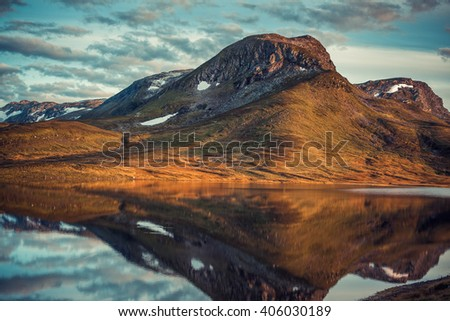 Mountains with reflection in lake in Norway. Autumn red film style colors. - stock photo