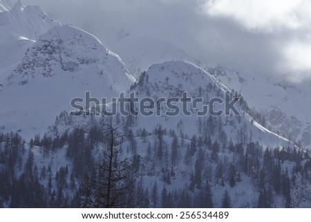 Mountains with snow and clouds at sidelight taken in the Swiss canton Ticino (Tessin).