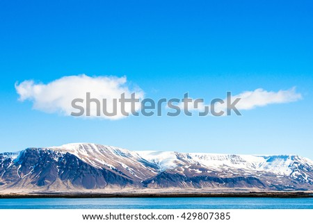 Mountains with snow by the arctic ocean - stock photo