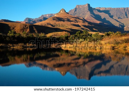 Mountains with symmetrical reflection in water, Royal Natal National Park, South Africa  - stock photo