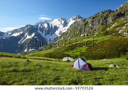 Mountaneer bivouac on meadow in mountains - stock photo