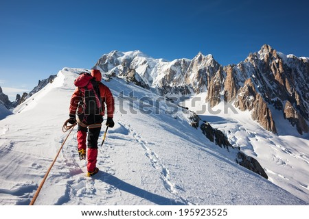 Mountaneer climbs a snowy ridge in Mont Blanc, France. Enterprise, diligence, team work: mountaneering concepts. - stock photo