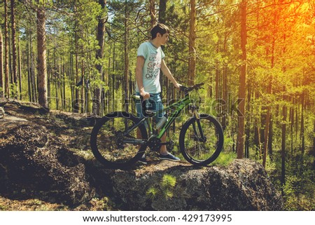 mountin biker with bike on the rocks. Successful happy rider on rocks holding bicycle. Sport, adventure, motivation and inspiration.