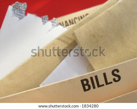 Mounting bills illustrating struggle with mounting debts. - stock photo