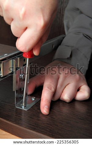 Mounting furniture, fitting Computer desk keyboard tray track drawer slide rail, screwing screw using a manual screwdriver. - stock photo