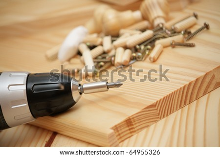 Mounting wooden furniture with cordless screwdriver - stock photo
