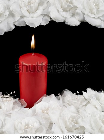 Mourning candle and white roses composition over black background