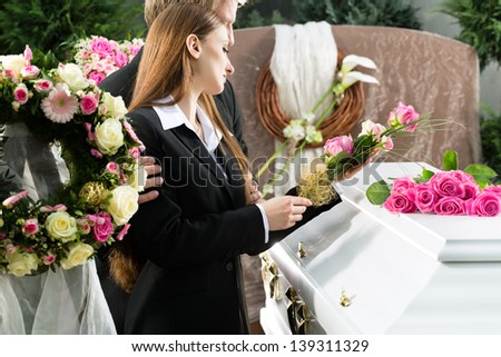 Mourning man and woman on funeral with pink rose standing at casket or coffin - stock photo